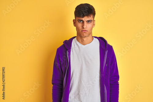 Fototapeta Young indian man wearing purple sweatshirt standing over isolated yellow background skeptic and nervous, frowning upset because of problem. Negative person. obraz na płótnie