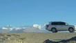 SLOW MOTION: Tourists on a fun adventure drive down the gravel road crossing the Tibetan Plateau. SUV drives along the gravel path offering a stunning view of the untouched glaciers in the Himalayas.