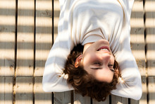 Young Woman Lays On Wooden Deck With  Shadow Cast Over Her Face