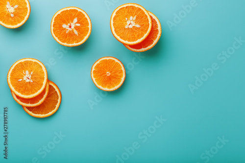 Fotografía  Slices and slices of orange pulp on a bright blue background as a textural background, the substrate