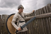 A Teenager Boy In A Historical Viking Costume With A Helmet And A Shield Holding A Sword Standing In The Middle Of A Wooden Fortress At A Historic Festival.