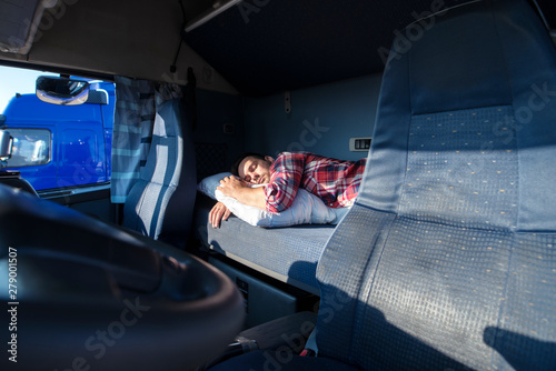Truck driver sleeping on bed inside truck cabin interior. Trucker lifestyle and people sleeping at job.