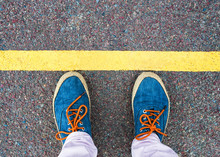 Women's Feet In Sneakers Standing At The Line.