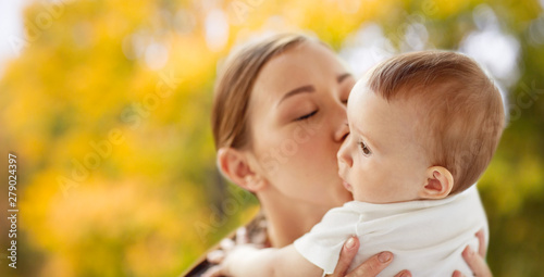 family, child and parenthood concept - close up of happy smiling young mother ki Canvas Print