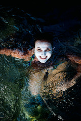 Blond woman with cucumber cream on face to care skin is submerged in water in river ..