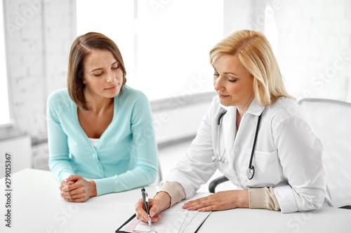 Obraz na plátně  medicine, healthcare and gynecology concept - female doctor with clipboard writi