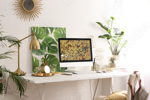 Modern workplace with computer and golden decor on desk near wall Wallpaper Mural