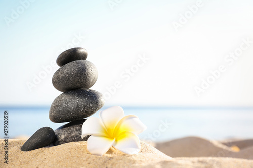 Fototapety, obrazy: Stack of dark stones and beautiful flower on sandy beach near sea, space for text. Zen concept