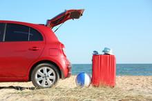 Modern Car, Bright Suitcase And Beach Accessories On Sand Near Sea