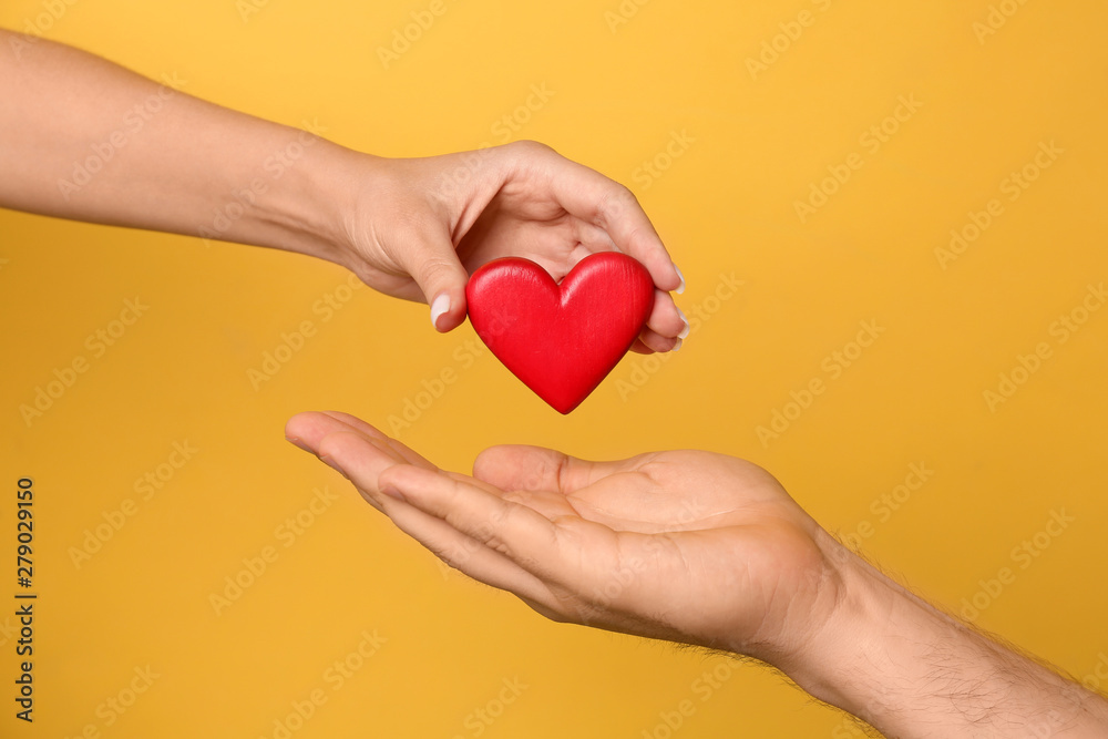 Fototapeta Woman giving red heart to man on yellow background, closeup. Donation concept