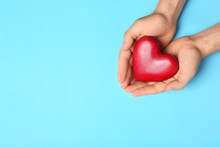 Young Man Holding Red Heart On Light Blue Background, Top View With Space For Text. Donation Concept