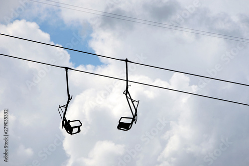 2 hanging chairs at old single seat chair lift against cloudy sky Canvas Print