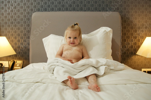 Poster Ecole de Danse Cute blonde baby girl sitting on the big bed