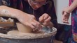 Young woman attaches the handle to the cup. Pottery workshop