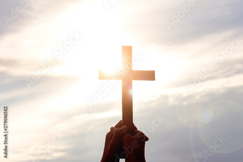 Fototapeta  human hands praying to the GOD while holding a crucifix symbol with bright sunbe