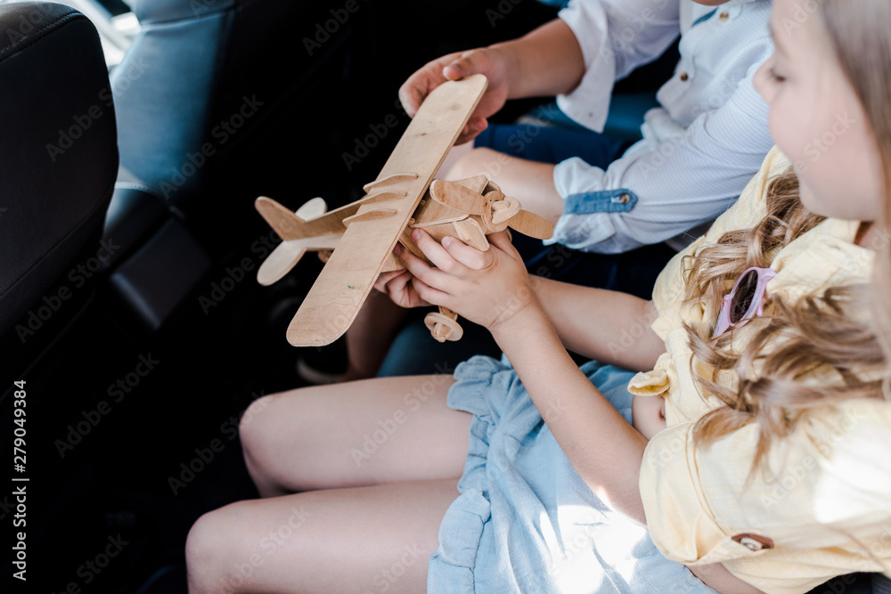 Fototapety, obrazy: cropped view of children playing with wooden biplane in car