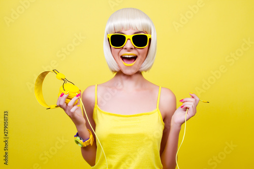 Girl in sun glasses with headphones on a yellow background. - 279050733