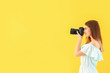 canvas print picture - Young female photographer on color background
