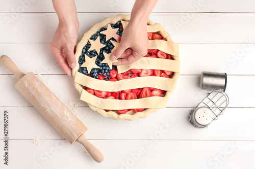 Woman making American flag pie in kitchen Tableau sur Toile
