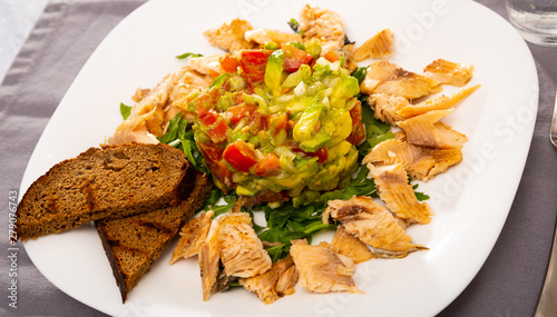 Salad guacamole with fresh tomatoes and arugula served with trout fillet