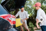 selective focus of happy man in cap putting travel bag in car trunk near son