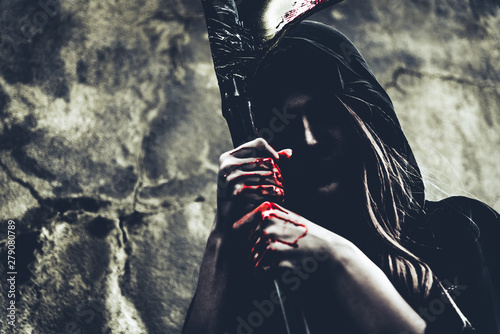 Photo  Demon witch with reaper standing in front of grunge wall background