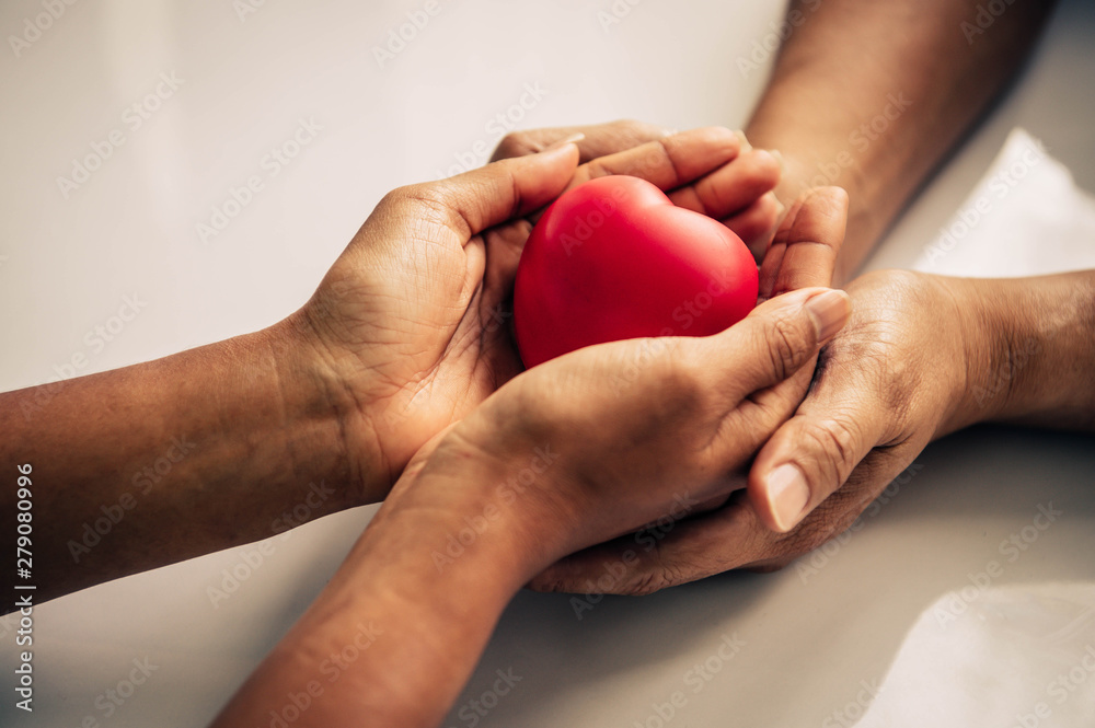 Fototapeta Helping hand of heart donor for patient in heart disease. Man give red heart to woman as couple. People lifestyle and couple romance. Healthcare and hospital medical concept. Symbolic of Valentine day