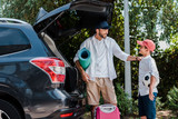 father holding fitness mat and looking at son with football near car