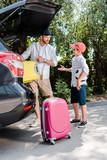 handsome father pointing with finger at baggage near son with football