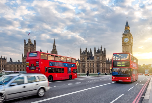 Houses of Parliament with Big Ben and double-decker buses on Westminster bridge at sunset, London, UK