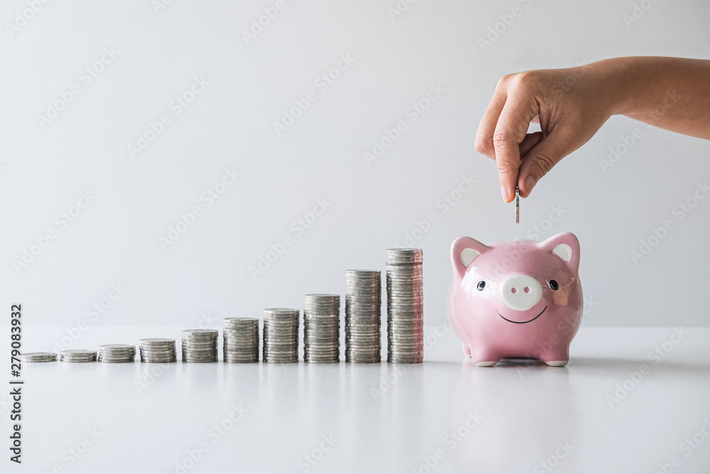 Fototapety, obrazy: Images of stacking coins pile and Hand putting coin into pink piggy bank for planning step up to growing and savings with money box, Saving money for future plan and retirement fund concept