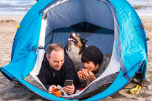 Couple Looking At The Smart Phone And Have Fun Inside A Tent In Free Camping On The Beach Dog Border Collie Behind Them Looking At The Camera. Bright Colors And Alternative Vacation Family Concept