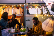 People Enjoying Camping Lifestyle And Van Life Travel Wanderlust - Caucasian Men And Woman Have Fun And Dinner Outside A Vintage Van - Evening Time With Lights And Romance