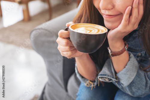 Fototapeta  Closeup image of a beautiful asian woman holding and drinking hot coffee in cafe