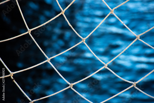 Fotografía  Fishing net and blue water surface