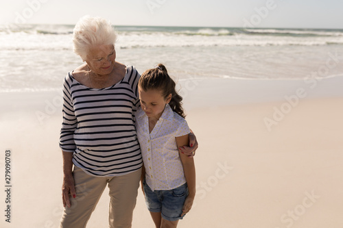 Senior woman and her granddaughter with arms around standing on beach