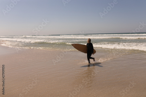 Senior female surfer walking with surfboard on the beach