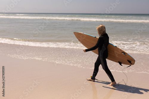 Side view of senior female surfer walking with surfboard on the beach
