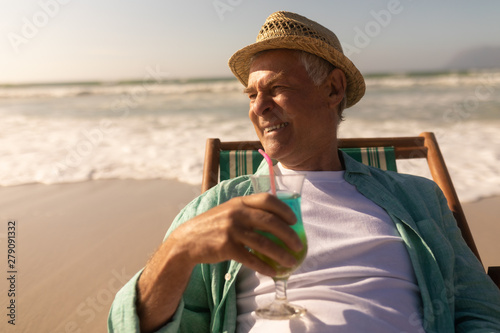 Senior man having cocktail drink while relaxing on sun lounger at beach