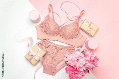 Obraz Female lace pink underwear with a pink ribbon and candles on a pink background. - fototapety do salonu
