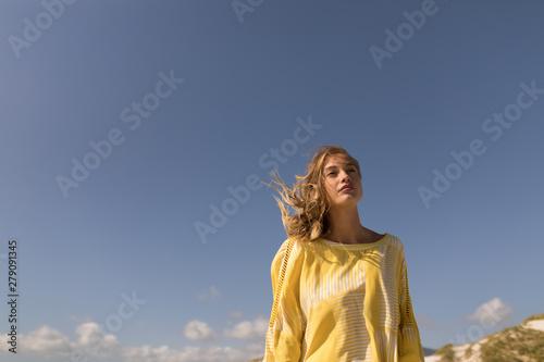 Beautiful young woman walking on beach