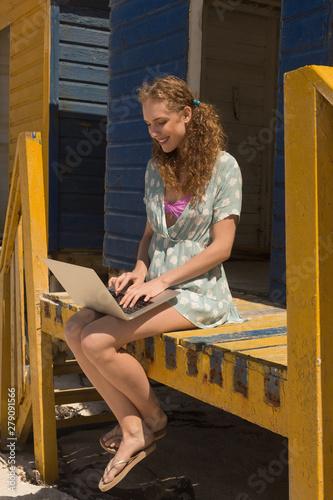Young Caucasian woman using laptop sitting on beach hut