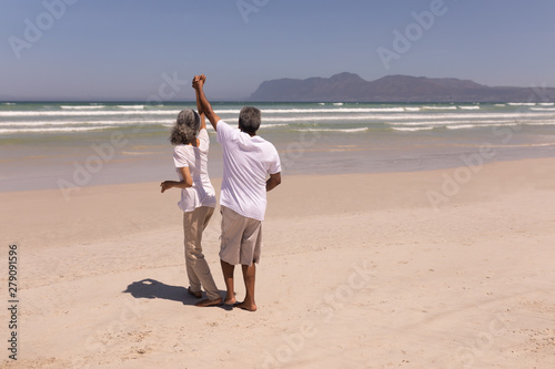 Senior couple dancing together on beach