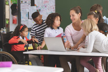 Teacher And Students Discussing Over Laptop In Classroom