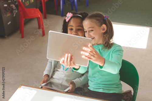 Overhead view of two school girls taking a photo with a digital tablet