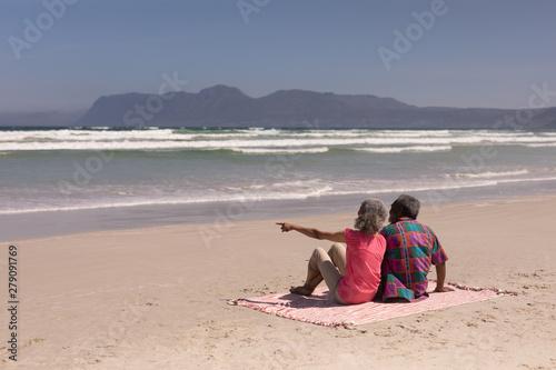 Senior couple sitting on blanket at beach