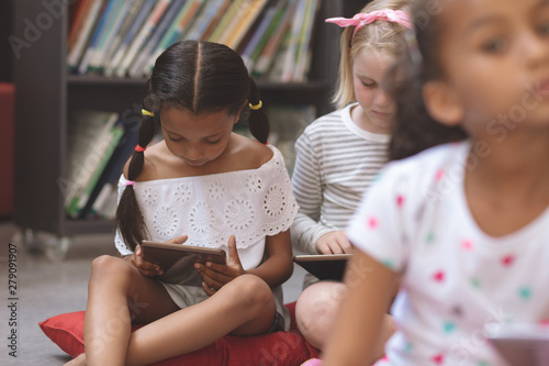 Mixte ethnicity schoolgirls holding digital tablet and sitting on cushions in a library