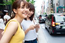 タクシーが来るのを待っている女性達