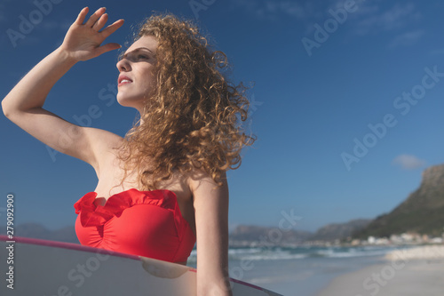 Female surfer holding surfboard at beach with shielding eye