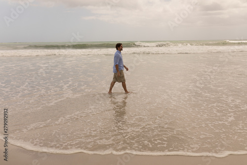 Side view of a man walking on the beach